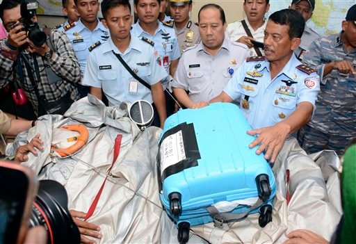 Commander of 1st Indonesian Air Force Operational Command Rear Marshall Dwi Putranto, right, shows airplane parts and a suitcase found floating on the water near the site where AirAsia Flight 8501 disappeared. (AP Photo/Dewi Nurcahyani)