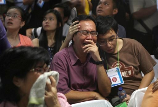 Relatives of passengers of the missing AirAsia Flight 8501 react upon seeing the news on television about the findings of bodies on the waters near the site where the jetliner disappeared Dec. 30, 2014. (AP Photo/Trisnadi)