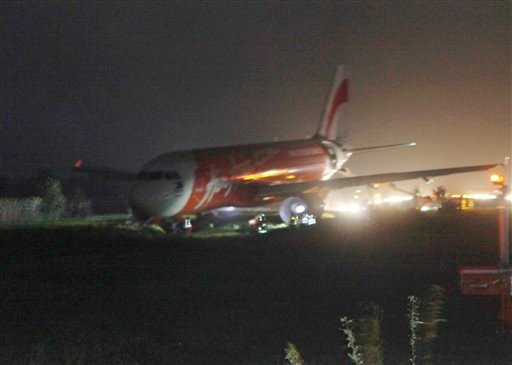 An AirAsia passenger plane sits on the grassy portion of the runway after overshooting upon landing in windy weather at Kalibo airport in Kalibo township, Aklan province in central Philippines Dec. 30, 2014. (AP Photo/Jun Aguirre)