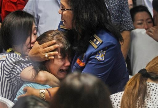Relatives of passengers of the missing AirAsia Flight 8501 react upon seeing the news on television about the findings of bodies on the waters near the site where the jetliner disappeared. (AP)
