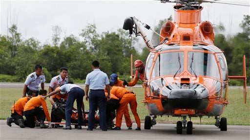 Officers of the National Search And Rescue Agency (BASARNAS) and Indonesian Air Force personnel unload a body of one of the victims on board AirAsia Flight 8501 at the airport in Pangkalan Bun, Indonesia Dec. 31, 2014. (AP Photo/Achmad Ibrahim)
