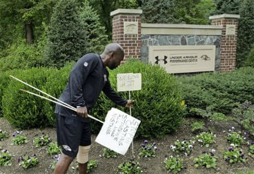 Sept. 8, 2014, file photo: Baltimore Ravens senior director of security Darren Sanders removes signs that were posted in support of former Ravens running back Ray Rice in front of the NFL football team's headquarters. (AP Photo/Patrick Semansky, File)