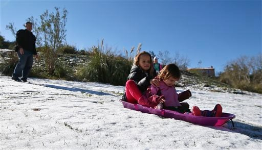 Ryanne Girard, 9, and her sister, Harper, 2, are stuck in the slush while they attempt to sled down a hill after a rare snow storm hits parts of Southern California Wednesday, Dec. 31, 2014, in Temecula, Calif. (AP)