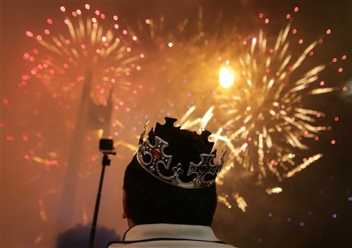 A Filipino watches a fireworks display at the Quezon Memorial Circle in suburban Quezon city, north of Manila, Philippines on Thursday, Jan. 1, 2015. (AP Photo/Aaron Favila)
