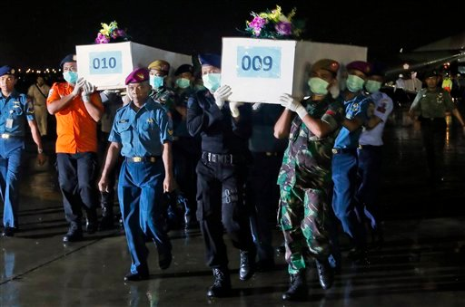 Indonesian military personnel carry coffins containing the bodies of victims of AirAsia Flight 8501 upon arrival at Juanda Naval Airbase in Surabaya, East Java, Indonesia, Friday, Jan. 2, 2015. After nearly a week of searching for the victims of AirAsia F