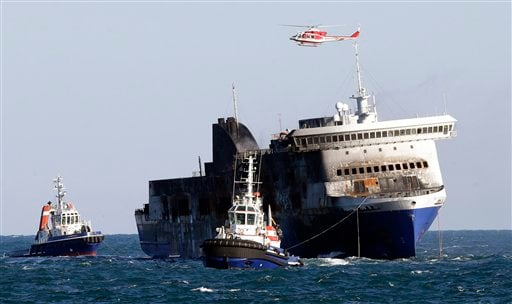 The Norman Atlantic ferry is being towed into the port of Brindisi, Italy, Friday, Jan. 2, 2015. The blaze that broke out Sunday and torched the ferry has killed at least 11 people and authorities prepared to search it for possible more dead. Italy says 4