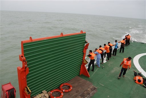 Members of the National Search And Rescue Agency (BASARNAS) stand on KN SAR Purworejo ship during a search operation for the victims of AirAsia flight QZ 8501 on the Java Sea, Indonesia, Saturday, Jan. 3, 2015. Indonesian officials were hopeful Saturday t