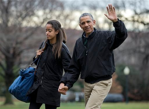 President Barack Obama, right, with his daughter Malia Obama, waves as they arrive at the White House in Washington, Sunday, Jan. 4, 2015, from a family vacation in Hawaii. (AP Photo/Manuel Balce Ceneta)