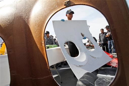 A crew member of Indonesian Navy ship KRI Bung Tomo holds a piece of the window panel of AirAsia Flight 8501 recovered in search operations for the ill-fated jetliner, during a press conference at the Navy's Eastern Fleet Naval Base in Surabaya, East Java