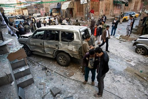 In this Tuesday, Dec. 23, 2014 file photo, Shiite Houthi men stand near a car damaged by a bomb explosion outside their house in Sanaa Yemen. Houthi rebels in September seized control of the capital, Sanaa, and are allied with loyalists of former preside