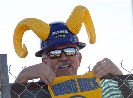 Rams fan Joe Ramirez stands behind a fence as officials with the Hollywood Park Land Company unveil a proposal for a new NFL stadium at Hollywood Park in Inglewood, Calif., Monday, Jan. 5, 2015.