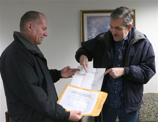 Tomas Berger, left, and James Gaunt show their paperwork for a pre-martial course at the Leon county courthouse as they apply for a marriage license on Tuesday, Jan. 6, 2015, in Tallahassee, Fla. U.S. District Judge Robert L. Hinkle's ruling that Florida'