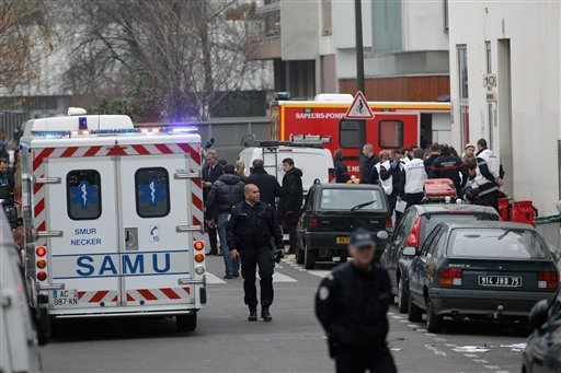 Police officers and firemen gather outside the French satirical newspaper Charlie Hebdo's office, in Paris, Wednesday, Jan. 7, 2015. (AP Photo/Thibault Camus)