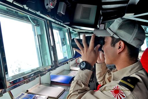 A crew member of Japan Maritime Self-Defense Force ship JS Onami uses his binoculars during a search operation for the victims of AirAsia Flight 8501 on the Java Sea, Indonesia Jan. 7, 2015. (AP Photo/Dewanto Samodro, Pool)
