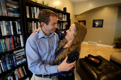 """Jeff Bennion and his wife Tanya stand in their home near Salt Lake City. Two Utah men set to appear in the reality TV show """"My Husband's Not Gay,"""" say they're fulfilled in their relationships to their wives. (AP Photo/Rick Bowmer)"""