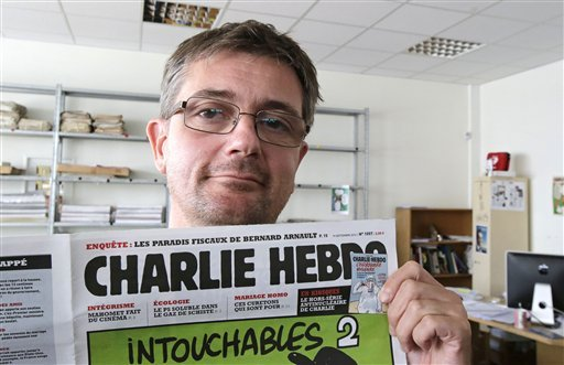 FILE - In this Sept.19, 2012 file photo, Stephane Charbonnier also known as Charb , the publishing director of the satyric weekly Charlie Hebdo, displays the front page of the newspaper as he poses for photographers in Paris. (AP)