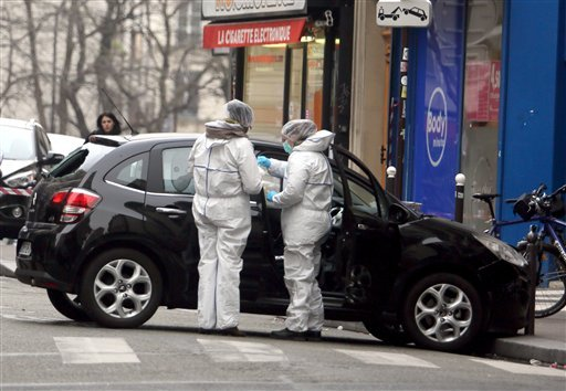 Forensic experts examine the car believed to have been used as the escape vehicle by gunmen who attacked the French satirical newspaper Charlie Hebdo's office, in Paris, France, Wednesday, Jan. 7, 2015. (AP)