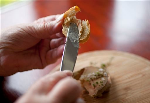 File - This July 17, 2012 file photo shows Karlene Bley of Los Angeles spread her torchon of foie gras onto bread during lunch at the Presidio Social Club restaurant in San Francisco. (AP)