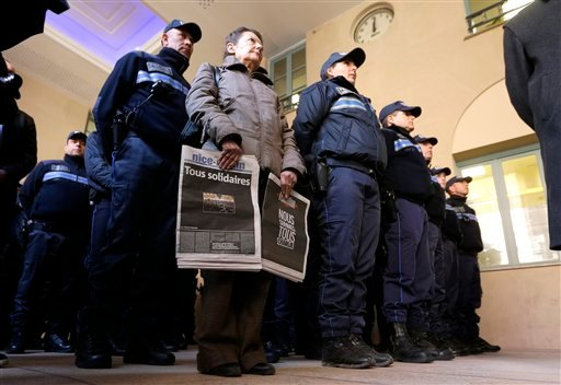"""A woman holding front pages of French newspapers reading """"All united"""", left and """"We are all Charlie"""", and Municipal police officers observe, a minute of silence for victims of the shooting at the satirical newspaper Charlie Hebdo, in Nice town hall. (AP)"""