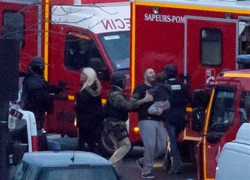 A security officer directs released hostages after they stormed a kosher market to end a hostage situation, Paris, Friday, Jan. 9, 2015. (AP Photo/Michel Euler)