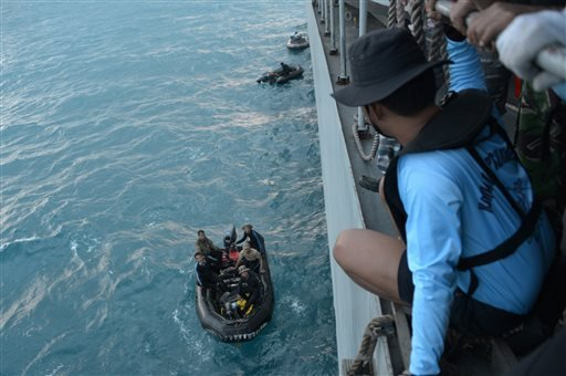Indonesian navy divers prepare operations to lift the tail of AirAsia Flight 8501 in Java sea, Indonesia Friday, Jan. 9, 2015. Days after sonar detected apparent wreckage, an unmanned underwater vehicle showed the plane's tail, lying upside down and parti
