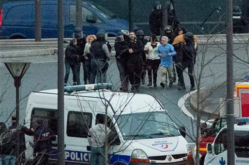 Security officers escort released hostages after they stormed a kosher market to end a hostage situation, Paris, Friday, Jan. 9, 2015. (AP)