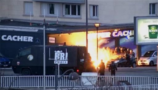 In this image taken from a video provided by PFMTV, police officers storm a kosher grocery to end a hostage situation in Paris, Friday, Jan. 9, 2015. (AP)