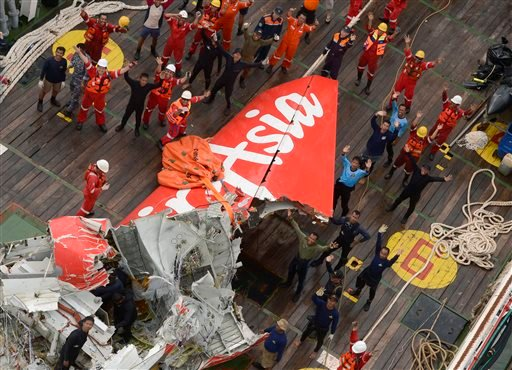 Rescuers wave at an Indonesian Air Force helicopter near portion of AirAsia Flight 8501 after it was recovered from the sea floor on the deck of a rescue ship on the Java Sea, Saturday, Jan. 10, 2015. Investigators searching for the crashed plane's black