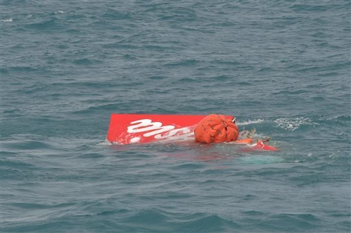 Portion of the tail of AirAsia Flight 8501 floats on the water as Indonesian navy divers conduct search operations for the black boxes of the crashed plane in the Java Sea, Indonesia, Saturday, Jan. 10, 2015. Investigators searching for black boxes in the