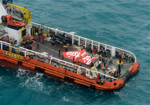 In this photo taken from an Indonesian Air Force Super Puma helicopter, portion of the tail of AirAsia Flight 8501 is seen on the deck of a rescue ship after it was recovered from the sea floor on the Java Sea, Saturday, Jan. 10, 2015. Investigators searc