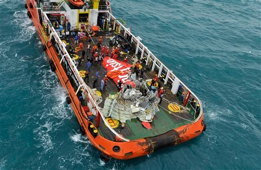 Portion of the tail of AirAsia Flight 8501 is seen on the deck of rescue ship after it was recovered from the sea floor on the Java Sea, Saturday, Jan. 10, 2015. Investigators searching for the crashed plane's black boxes lifted the tail portion of the je