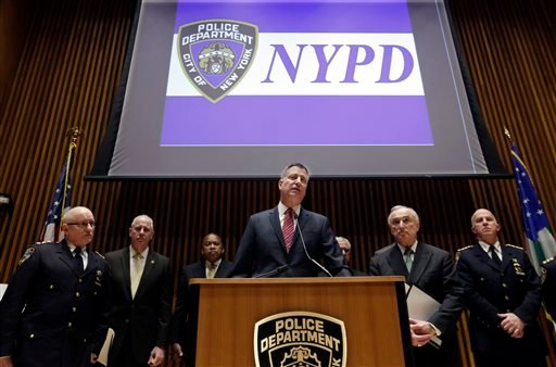 In this Jan. 5, 2015 photo, New York Mayor Bill de Blasio, center, accompanied by New York City Police Commissioner William Bratton, second from right, and other ranking NYPD officers, addresses a news conference at New York City Police headquarters, Mond