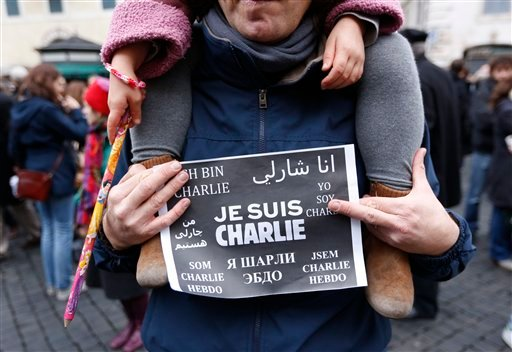 "A man holds a sign ""Je Suis Charlie"" (I am Charlie) signs as several hundred people gather in solidarity with victims of two terrorist attacks in Paris, one at the office of weekly newspaper Charlie Hebdo and another at a kosher market, in front of the Fr"