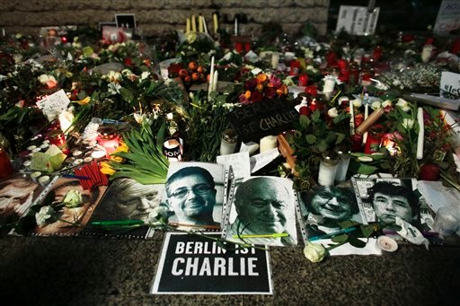 Photos of victims of the Paris terror attacks and a poster reading 'Berlin is Charlie' have been placed with flowers and candles in front of the French embassy in Berlin Sunday Jan. 11, 2015. Several thousand people gathered in solidarity with victims of