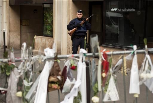 A French police officer stands guard on a road leading to the offices of French satirical newspaper Charlie Hebdo in Paris, Saturday, Jan. 10, 2015. France's government urged the nation to remain vigilant Saturday, as thousands of security forces try to t