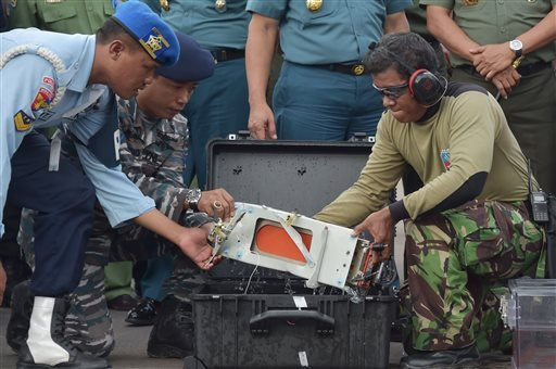 Indonesian military personnel remove Flight Data Recorder of the ill-fated AirAsia flight QZ8501 into a proper case in Pangkalan Bun, Indonesia, Monday, Jan. 12, 2015. Divers retrieved one black box Monday and located the other from the AirAsia plane that