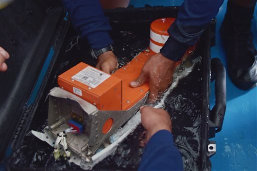 Indonesian divers hold FDR (Flight Data Recorder) of the AirAsia flight QZ8501 onboard the navy vessel KRI Banda Aceh, Monday, Jan. 12, 2015. Divers retrieved one black box Monday and located the other from the AirAsia plane that crashed more than two wee