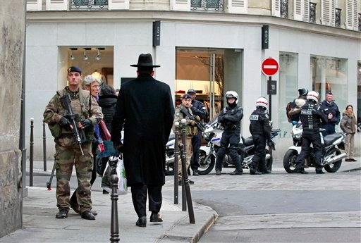Police officers and French army soldiers patrol Rue des Rosiers street, in the heart of Paris Jewish quarter, in Paris, Monday Jan. 12, 2015. France on Monday ordered 10,000 troops into the streets to protect sensitive sites after three days of bloodshed
