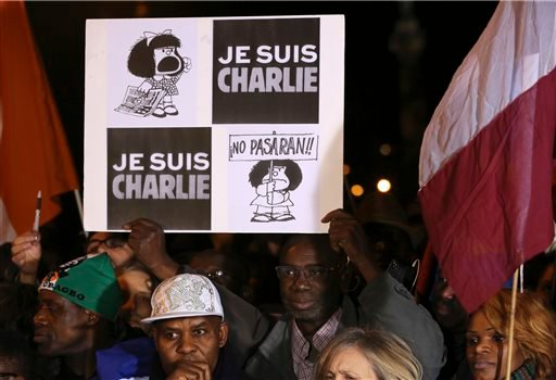 """A man holds up a placard that reads """"I am Charlie"""" at the Place de la Nation in Paris Sunday, Jan. 11, 2015. More than 40 world leaders, their arms linked, marched through Paris Sunday to rally for unity and freedom of expression and to honor 17 victims o"""