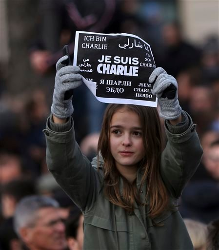 """A girl holds up a placard that reads """"I am Charlie"""" in several languages at the Place de la Nation in Paris Sunday, Jan. 11, 2015. More than 40 world leaders, their arms linked, marched through Paris Sunday to rally for unity and freedom of expression and"""