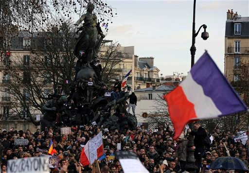 """People wave national flags and hold placards that read """"I am Charlie"""" at the Place de la Nation in Paris, France, Sunday, Jan. 11, 2015. More than 40 world leaders, their arms linked, marched through Paris Sunday to rally for unity and freedom of expressi"""