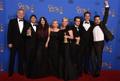 "Jonathan Sehring, from left, Richard Linklater, Lorelei Linklater, Cathleen Sutherland, Patricia Arquette, Ellar Coltrane, John Sloss, and Ethan Hawke pose in the press room with the award for best motion picture - drama for ""Boyhood"" at the 72nd annual G"