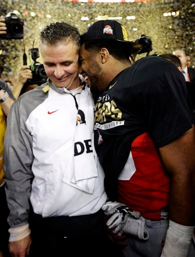 Ohio State head coach Urban Meyer and Ezekiel Elliott celebrate after the NCAA college football playoff championship game against Oregon Monday, Jan. 12, 2015, in Arlington, Texas. Ohio State won 42-20.