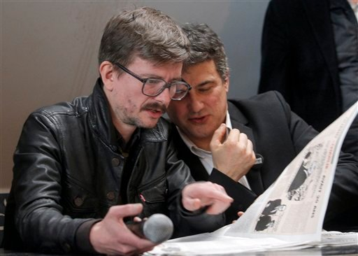 Renald Luzier, known as Luz, left, and columnist Patrick Pelloux, look at the Charlie Hebdo paper during a press conference in Paris, France, Tuesday, Jan. 13, 2015. (AP)