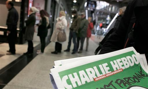 People queue up to buy the new issue of Charlie Hebdo newspaper at a newsstand in Paris Wednesday, Jan. 14, 2015. (AP Photo/Christophe Ena)