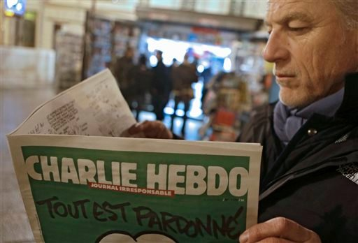 Jean Paul Bierlein reads the latest issue of Charlie Hebdo outside a newsstand in Nice, southeastern France, Wednesday, Jan. 14, 2015. (AP)