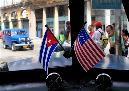 In this March 22, 2013 file photo, miniature flags representing Cuba and the U.S. are displayed on the dash of an American classic car in Havana, Cuba. (AP Photo/Franklin Reyes, File)