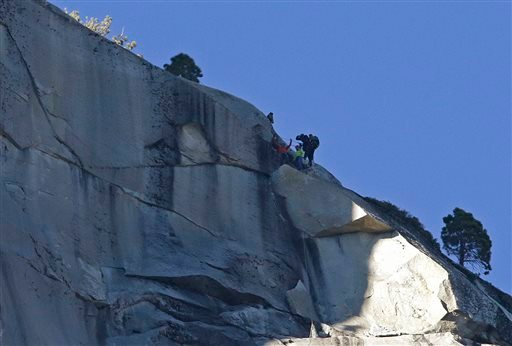 Kevin Jorgeson, bottom left, raises his arms beside Tommy Caldwell after both reached the summit of El Capitan, Jan. 14, 2015, as seen from the valley floor in Yosemite National Park, Calif. (AP Photo/Ben Margot)