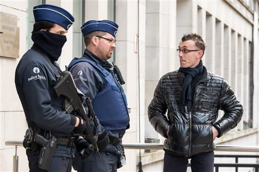 Police talk to a man at the entrance of a government building in Brussels, Friday, Jan. 16, 2015. Thirteen people were detained in Belgium and two arrested in France in an anti-terror sweep following a firefight in which two suspected terrorists were kill