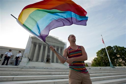 FILE - In this June 26, 2013, file photo, gay rights advocate Vin Testa waves a rainbow flag in front of the Supreme Court in Washington. (AP)
